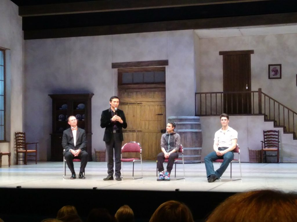 Li Cunxin speaking on stage with conductor and dancers seated on stage